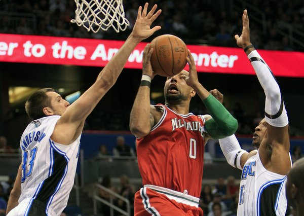 Milwaukee Bucks' Drew Gooden (0) gets between Orlando Magic's Ryan Anderson (33) and Dwight Howard for a shot in the first half of an NBA basketball game, Saturday, March 3, 2012, in Orlando, Fla.