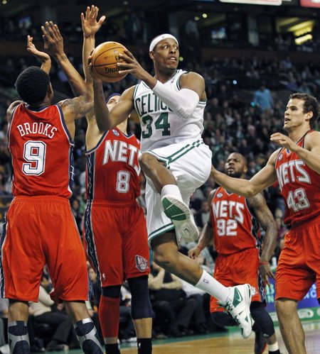 Boston Celtics forward Paul Pierce (34) looks to pass as he is surrounded by New Jersey Nets guard MarShon Brooks (9), guard Deron Williams (8), guard DeShawn Stevenson (92) and forward Kris Humphries (43) during the first quarter of an NBA basketball game in Boston, Friday, March 2, 2012.