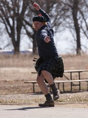 Kilt-clad Billy Williams winds up as he throws a bowl during an Irish road bowling tournament on Sunday at Clinton Lake State Park. The goal of Irish road bowling is to roll a 28-ounce iron cannonball around the course. The winner is determined by whoever makes it around the course in the least amount of throws.