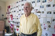 Robert Ford stands in his living room that has one complete wall decorated with Valentine cards in College Hill on Feb. 16. At age 98, the only thing Wichitan Robert Ford told his family he wanted was some cards for Christmas, and he now is a pen pal to students in Georgia.