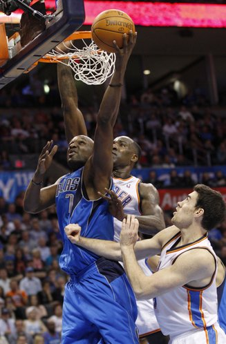Dallas Mavericks forward Lamar Odom (7) shoots in front of Oklahoma City Thunder's Kendrick Perkins, center, and Nick Collison in the first quarter of an NBA basketball game in Oklahoma City, Monday, March 5, 2012.