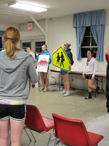 Sophia Lehman (with car sign) and Allie Webb (with school crossing sign), both Eudora High School students, participate in pedestrian safety workshop that teaches second graders tips to remember when walking to school.