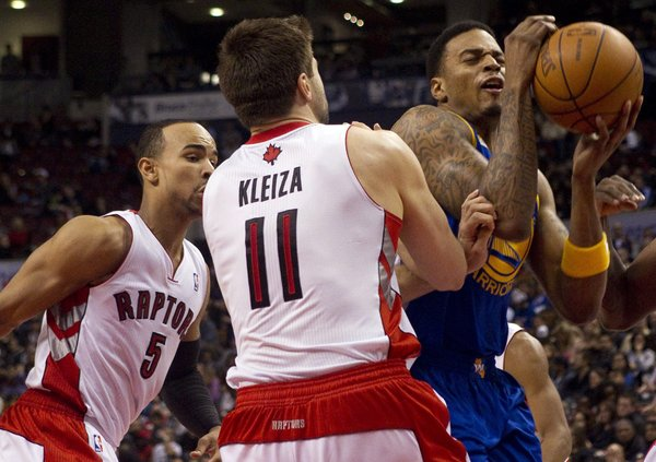 Golden State Warriors Brandon Rush, right, tries to drive through Toronto Raptors' Jerryd Bayless, left, and Linas Kleiza (11) during the second half of an NBA basketball game in Toronto on Sunday, March 4, 2012.
