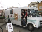 """Sarah Herrmann looks at cards she's just purchased from Kyle Durrie's """"type truck,"""" parked outside Wonder Fair gallery, 803 Mass., on March 7, 2012."""