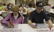 Marian and Wayne Boedeker, of Kansas City, Kan., scan their bingo cards during a game of bingo on March 7 at the American Legion post, 3408 W. Sixth St.
