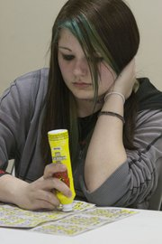 "Fourteen-year-old Allison Lane marks her bingo card during a March 7 game at the American Legion post on West Sixth Street. ""I don't care if my friends call me a dork,"" said Allison, a Liberty Memorial Central Middle School student. ""At least I'm not wasting my time getting in trouble, and I'm with my family doing something decent."""