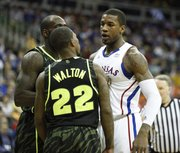Kansas forward Thomas Robinson gets in the face of Baylor guard A.J. Walton as Baylor forward Quincy Acy intervenes during the first half on Friday, March 9, 2012.