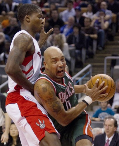 Milwaukee Buck Drew Gooden drives to the net past Toronto Raptor Ed Davis during first half NBA play in Toronto on Sunday, March 11, 2012.