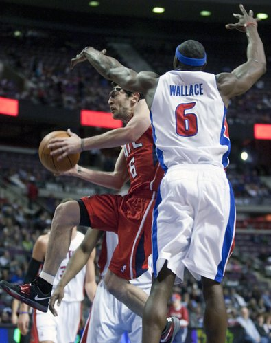 Atlanta Hawks' Kirk Hinrich, left, goes to the basket past Detroit Pistons' Ben Wallace, right, during the first half of an NBA basketball game Friday, March 9, 2012, in Auburn Hills, Mich.