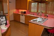 The blinding pink kitchen contains every 1950s modern convenience.