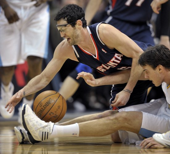 Atlanta Hawks' Kirk Hinrich, top, reaches for a loose ball against Denver Nuggets' Danilo Gallinari, of Italy, in the third quarter of their NBA basketball game in Denver, Tuesday, March 13, 2012.
