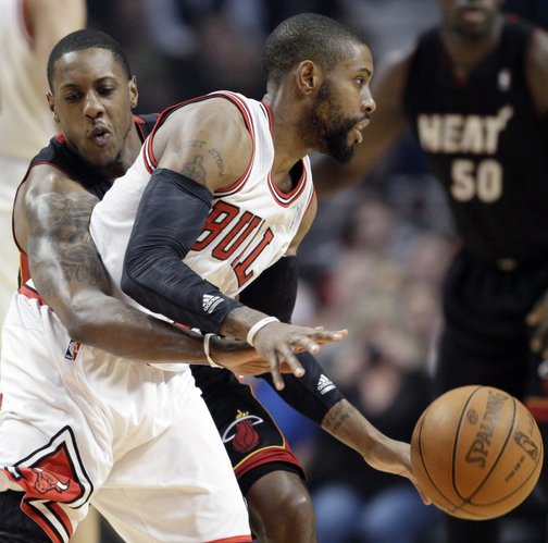 Chicago Bulls guard C.J. Watson (7) controls the ball as Miami Heat guard Mario Chalmers (15) guards during the first half of an NBA basketball game in Chicago, Wednesday, March 14, 2012.