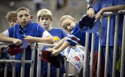 Young Kansas fans from Omaha, Hunter Thyfault, 5, right, Peter Crane, 11, and Dylan Thyfault, 11, anxiously await the arrival of the Jayhawks for practice at Century Link Center in Omaha on Thursday, March 15, 2012.