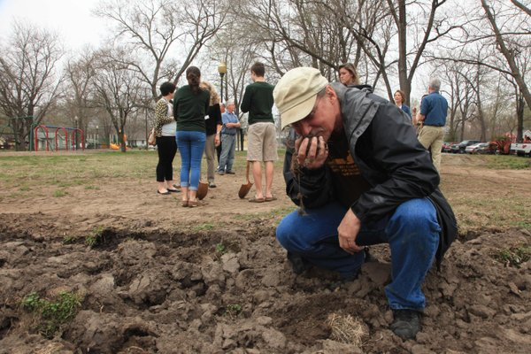 Stu Shafer, coordinator of the sustainable agriculture program at Johnson County Community College, sniffs the freshly-turned earth before a ground-breaking ceremony for the City of Lawrence's Common Ground program. The ceremony was Friday, March 16, 2012, near  John Taylor Park in north Lawrence.