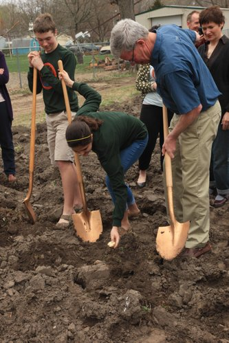 Hayley Luna plants a potato as T.J. Everett, left, and Lawrence Vice Mayor Bob Schumm look on. They helped officially break ground on the city's Common Ground program Friday, March 16, 2012, at John Taylor Park in north Lawrence. Everett and Luna are members of the student garden project at West Middle School.