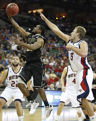 Purdue guard Lewis Jackson gets past Saint Mary's forward Mitchell Young for a bucket during the second half on Friday, March 16, 2012 at CenturyLink Center in Omaha. At left is Saint Mary's forward Rob Jones.