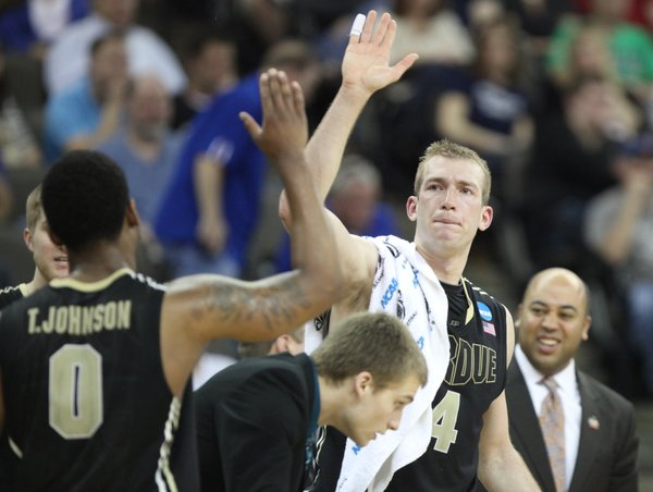 Purdue forward Robbie Hummel (4) reaches high to slap hands with teammate Terone Jonnson during the second half on Friday, March 16, 2012 at CenturyLink Center in Omaha.