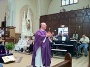 Father Tom Fangman claps during Mass at Sacred Heart Church in Omaha, Neb. Fangman is a 1985 Kansas University graduate and joins in the Rock Chalk chant during certain Masses at his parish.