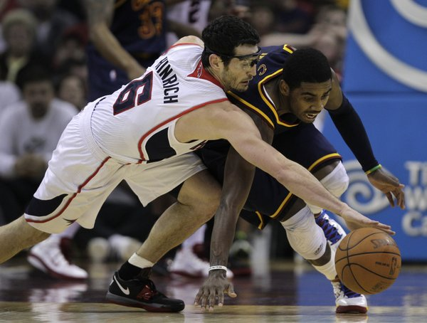 Atlanta Hawks' Kirk Hinrich (6) and Cleveland Cavaliers' Kyrie Irving (2) fight for a loose ball in the second quarter of an NBA basketball game in Cleveland on Sunday, March 18, 2012.