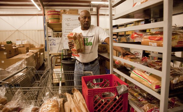 Volunteer Charles Tolbert, a former client, restocks some of the shelves at Just Food on Tuesday, March 20, 2012.