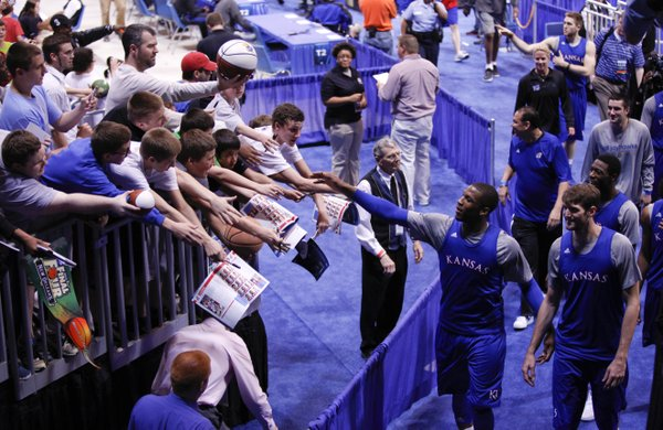 Kansas player Thomas Robinson reaches to slap hands with fans wanting autographs as the Jayhawks' are ushered off the court at the Edward Jones Dome in St. Louis.