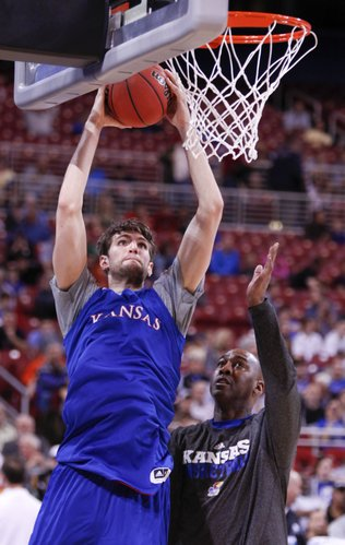 Kansas center Jeff Withey elevates for a dunk during drills with assistant coach Danny Manning at the Edward Jones Dome in St. Louis.