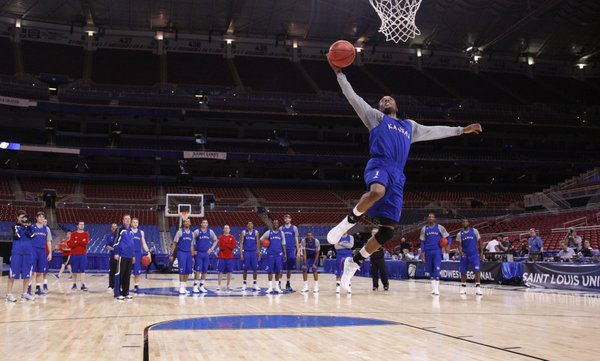 The Jayhawks watch as Naadir Tharpe goes up for a dunk to end practice at the Edward Jones Dome in St. Louis. Tharpe missed and was ordered by head coach Bill Self to do pushups.