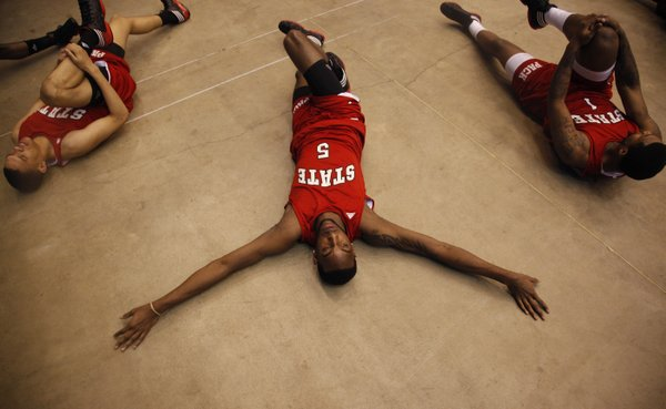 North Carolina State forward C.J. Leslie stretches out between teammates Tyler Harris, left, and Richard Howell during a day of press conferences and practices at the Edward Jones Dome in St. Louis.