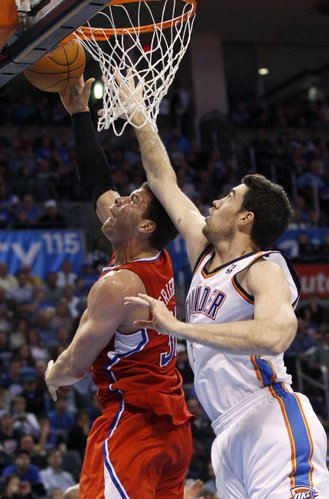 Los Angeles Clippers forward Blake Griffin, left, shoots in front of Oklahoma City Thunder center Nick Collison during the first quarter of an NBA basketball game in Oklahoma City, Wednesday, March 21, 2012.