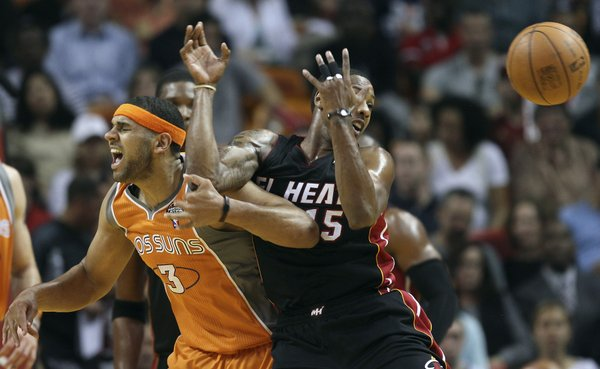 Phoenix Suns' Jared Dudley (3) and Miami Heat's Mario Chalmers (15) battle for the ball during the first half of an NBA basketball game in Miami, Tuesday, March 20, 2012.