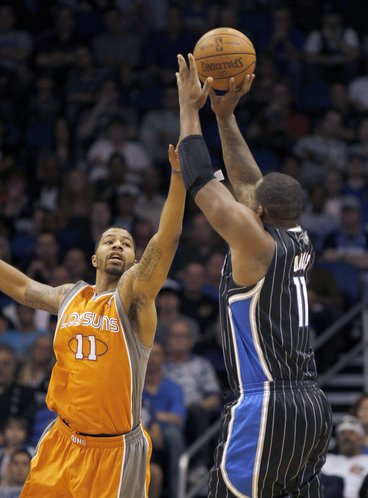 Orlando Magic forward Glen Davis, right, shoots over Phoenix Suns forward Markieff Morris during the first half of an NBA basketball game, Wednesday, March. 21, 2012, in Orlando Fla.