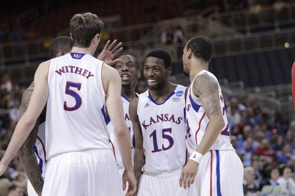 Elijah Johnson (15) along with from left, Jeff Withey, Tyshawn Taylor, and Travis Releford, laugh during a huddle in the second-half of the Jayhawks 60-57 win over North Carolina State in St. Louis Friday, March 16, 2012...