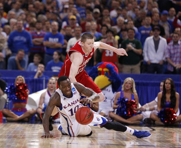 Kansas guard Tyshawn Taylor regains possession as North Carolina State forward Scott Wood defensds late in the second half on Friday, March 23, 2012 at the Edward Jones Dome in St. Louis.