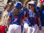 Kansas' Maggie Hull, right, and Liz Kocon (9) celebrate Hull's two-run homer run during the second game of a three-game series with Oklahoma State Saturday, March 24, 2012 at Arrocha Ballpark.
