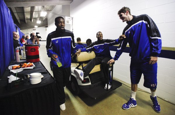 Kansas forward Thomas Robinson, center, jokingly pushes center Jeff Withey away from his golf cart as the players prepare to be shuttled to interviews on Saturday, March 24, 2012 at the Edward Jones Dome in St. Louis. At left is KU guard Elijah Johnson.