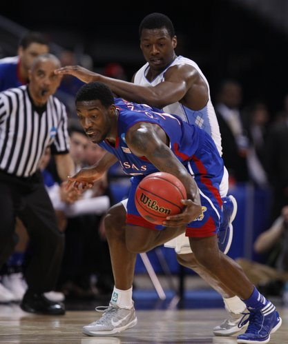 Kansas guard Elijah Johnson comes away with a steal from North Carolina forward Harrison Barnes during the first half on Sunday,  March 25, 2012 at the Edward Jones Dome in St. Louis.