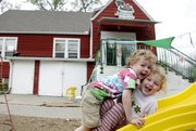 Rhys Fife, left, and Cecilia Divine-Devictor play outside the Lawrence Community Nursery School, the second-oldest nursery school cooperative in the country and one of Lawrence's many co-ops.