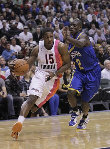 Miami Heat guard Mario Chalmers, let, drives on Indiana Pacers guard Darren Collison in the first half of an NBA basketball game in Indianapolis, Monday, March 26, 2012.