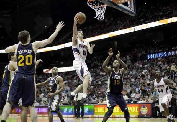 Atlanta Hawks' Kirk Hinrich (6) puts up a basket between Utah Jazz' Gordon Hayward (20) and Derrick Favors during triple overtime of an NBA basketball game, Sunday, March 25, 2012, in Atlanta. Atlanta won 139-133 in the NBA's first quadruple-overtime game since 1997.