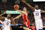 Kansas defenders Thomas Robinson (0) and Elijah Johnson (15) defend as Ohio State guard Aaron Craft heads to the bucket during the first half on Saturday, March 31, 2012 at the Superdome.
