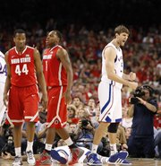 Kansas center Jeff Withey pumps his fist as Ohio State players William Buford (44) and Deshaun Thomas (1) show their frustration during a Jayhawk run in the second half.