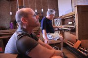 Proctor Crow, a Reuter Organ employee, plays the organ at First Presbyterian Church as Tracy Resseguie, the musical director at the church, listens March 31.