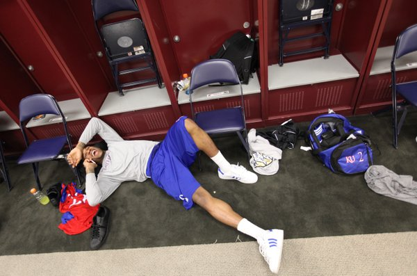 Kansas forward Thomas Robinson laughs with his phone up to his ear as he relaxes on the floor of the locker room after interviews on Sunday, April 1, 2012 at the Superdome.