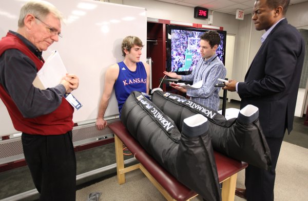 Kansas guard Conner Teahan sits in inflatable compression sleeves for his legs as he answers questions from media members during a press conference on Sunday, April 1, 2012 at the Superdome. Teahan says the compression helps push lactic acid from the muscles.