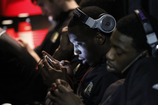 Tyshawn Taylor, center, and Elijah Johnson text and listen to music in an interview waiting room during press conferences in the Superdome Sunday.