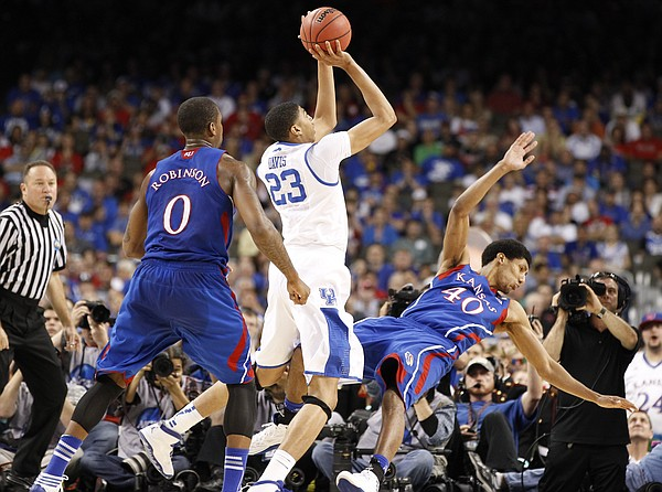Kansas forward Kevin Young takes a charge from Kentucky center Anthony Davis during the first half of the national championship on Monday, April 2, 2012 in New Orleans.
