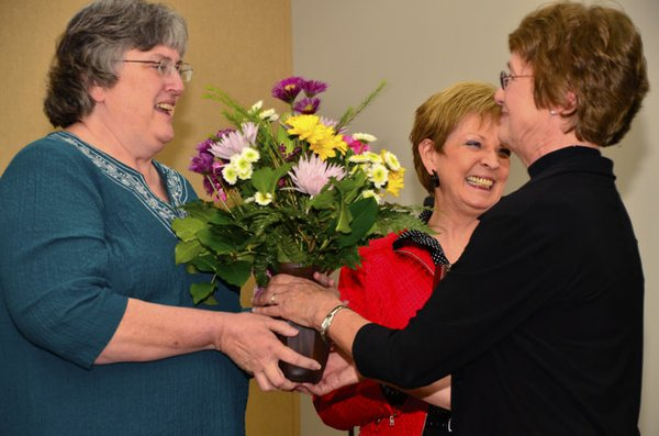 Pat Meyers, Lawrence-Douglas County Health Department clinic office coordinator, receives flowers from Kay Kent, namesake of the Kay Kent Excellence in Public Health Service Award. Kent served as director of the Health Department for 33 years. Also pictured is Shirley Martin-Smith, chair of the Lawrence-Douglas County Health Board.