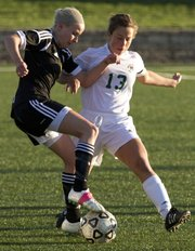 Shawnee Mission West midfielder Emily Franchett, left, uses her arm to hold off Free State sophomore Allix Ice during their soccer match Thursday, April 5, 2012 at FSHS.