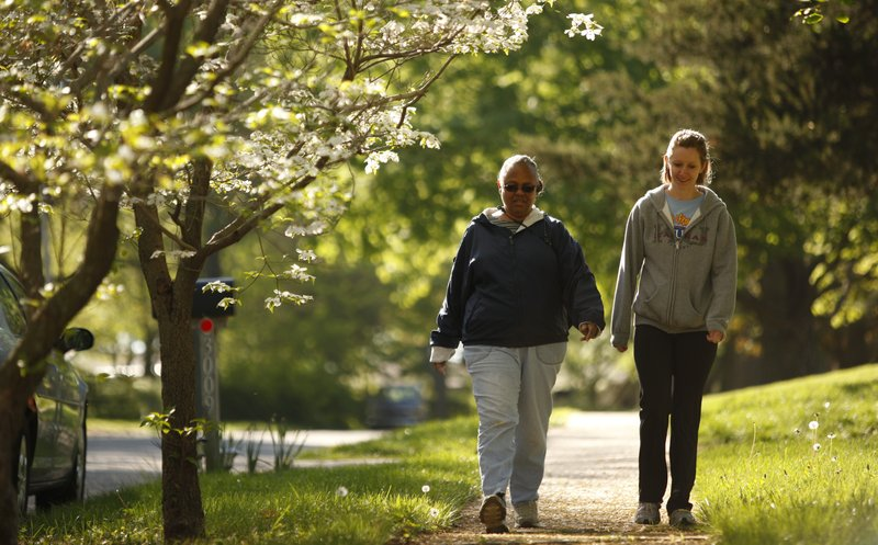 Lawrence resident Juin Thomas, 63, walks with Health Care Access wellness intern Jordan Ramey in a neighborhood near Holcom Park on Friday, April 6, 2012. Thomas has been participating in a wellness program offered by Health Care Access for two years and she believes it has helped maintain her health.