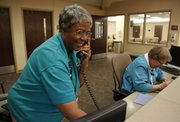 Lawrence Memorial Hospital volunteer Joanne Hurst takes a phone call from the registration desk next to fellow volunteer Corinne Geddings on Friday, April 6. Hurst has been volunteering with LMH for nine years and prior to that served on the board of trustees.